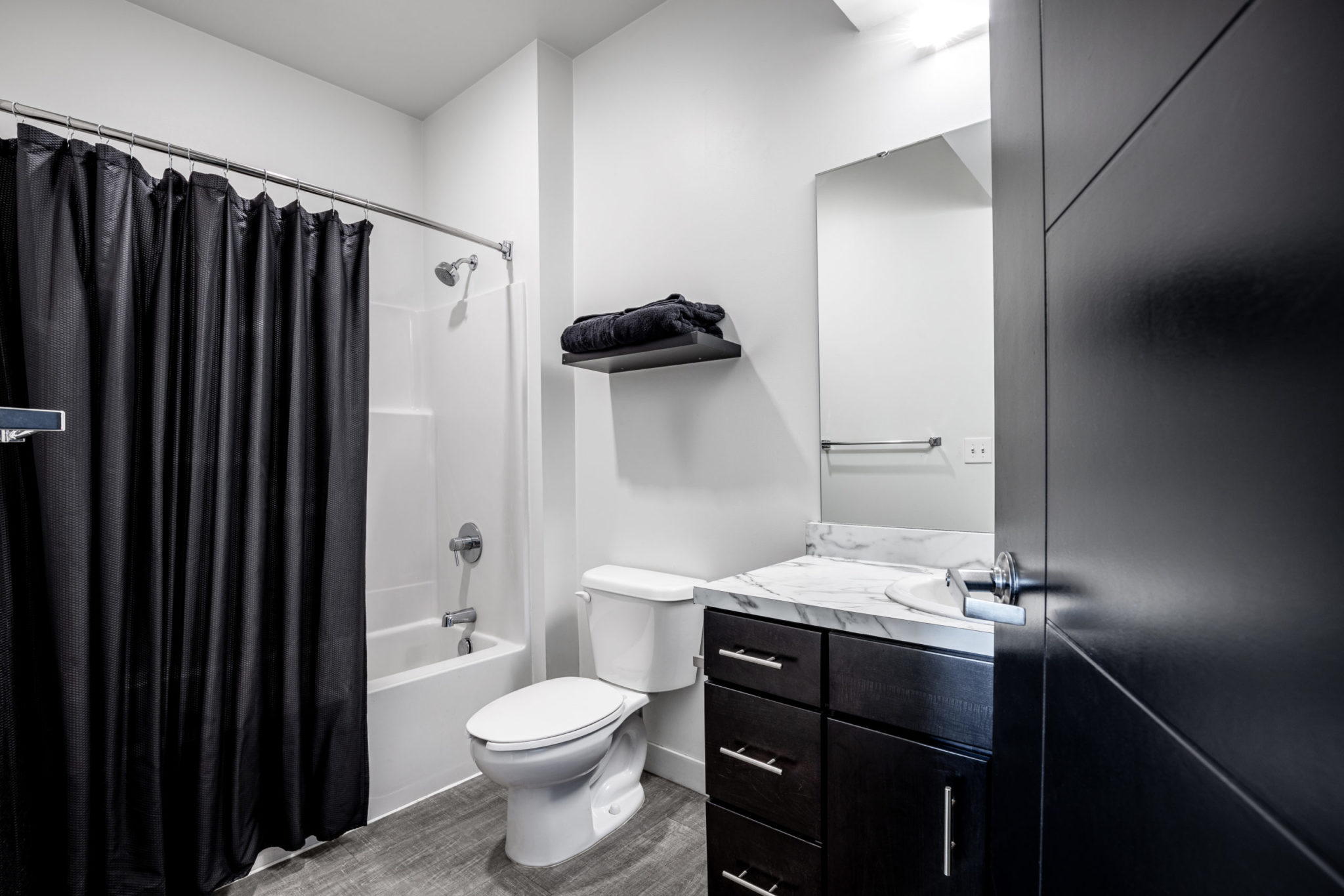 Modern minimal black and white bathroom with black shower curtains