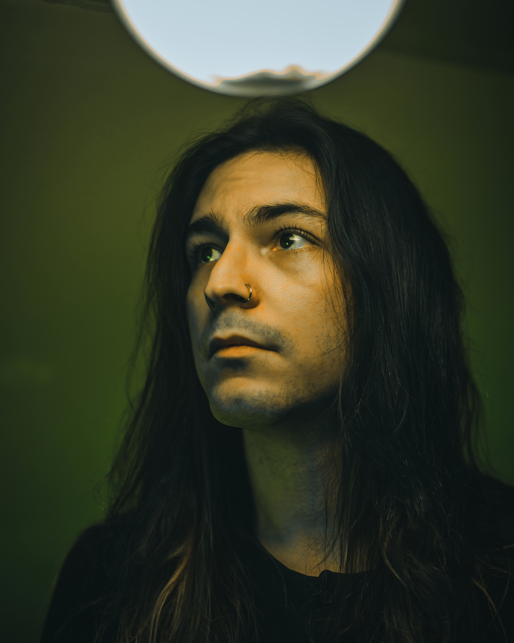 stoic pose of long black haired male looking off into the distance