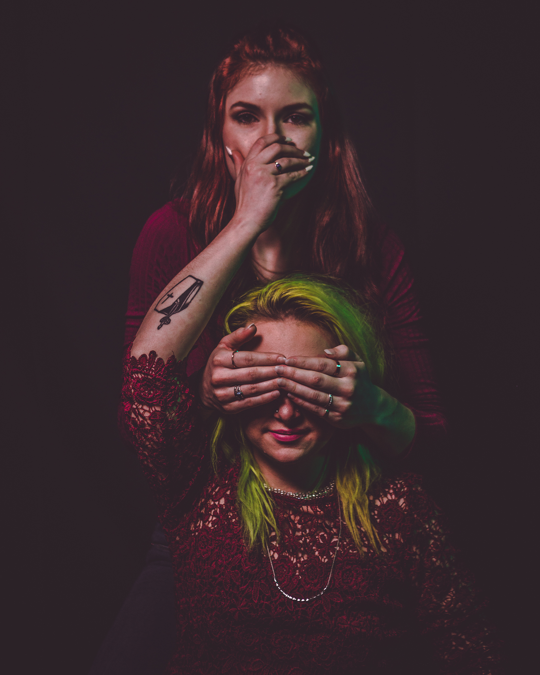 moody photograph of two females with red and green hair creating see no evil, hear no evil, speak no evil